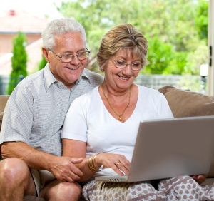 Senior couple using a laptop on the couch